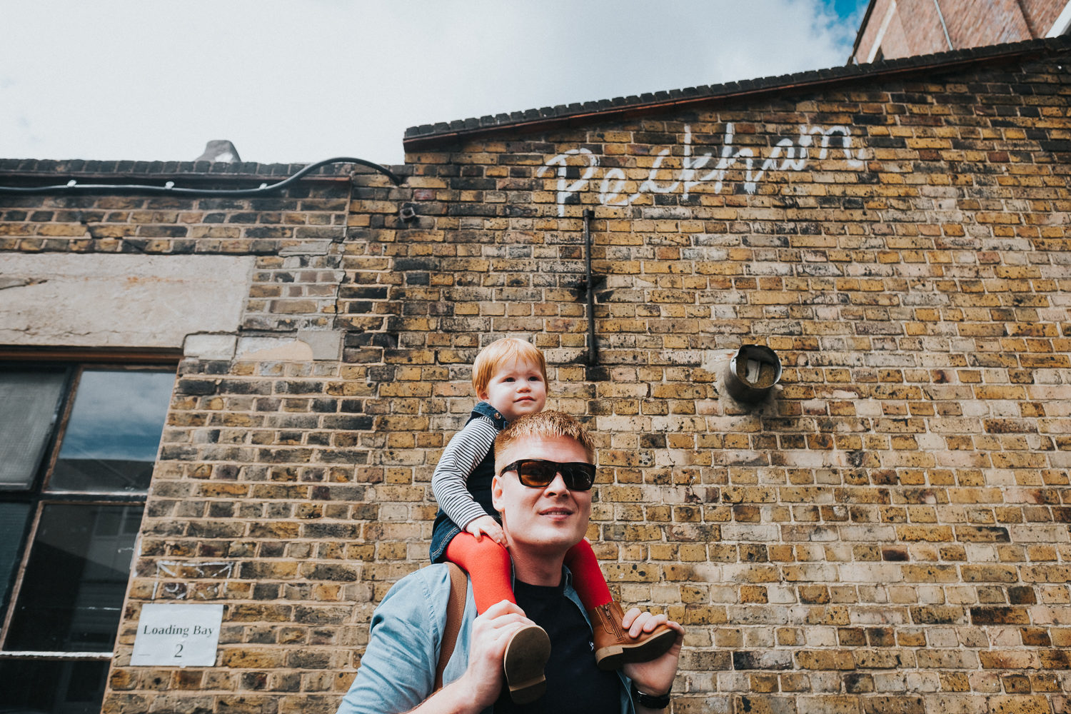 peckham family photo shoot little girl on dads shoulders by peckham street art wall