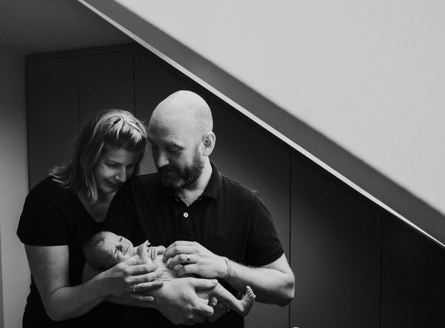 Ealing newborn photographer london baby photos parents with new baby standing next to window