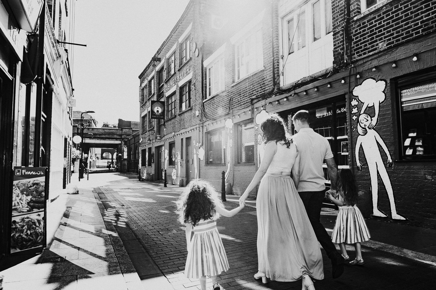 family photo shoot in shoreditch twin girls black and white photo family walking from behind