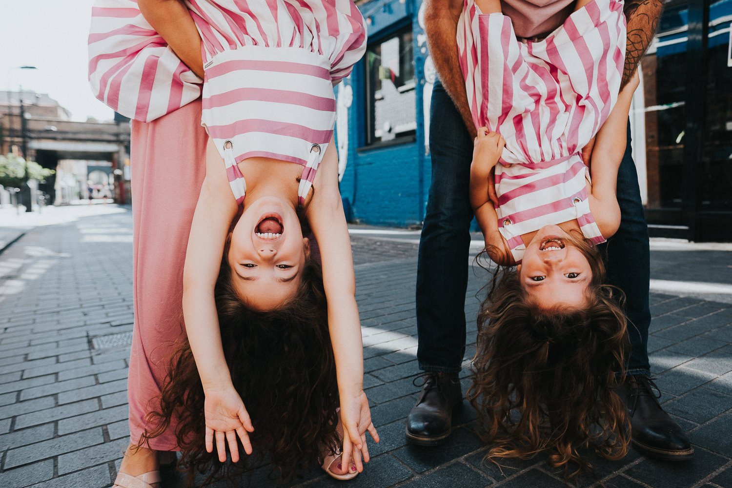family photo shoot in shoreditch twin girls family pink dresses hanging upside down