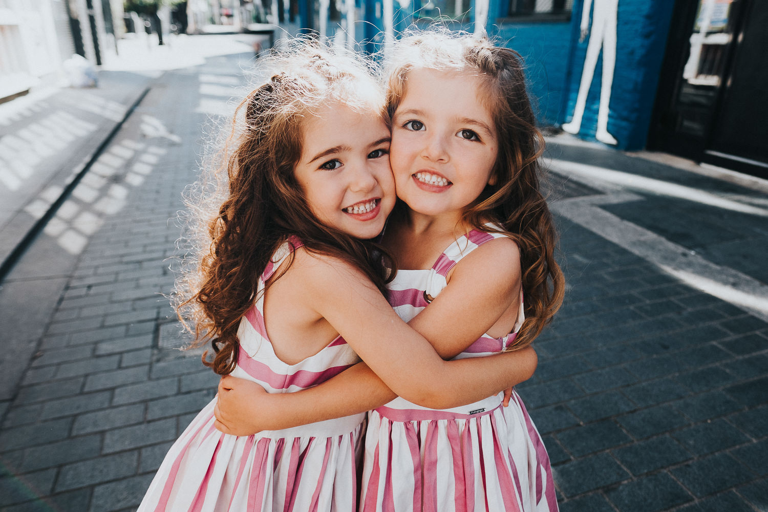 family photo shoot in shoreditch twin girls hugging in pink dresses