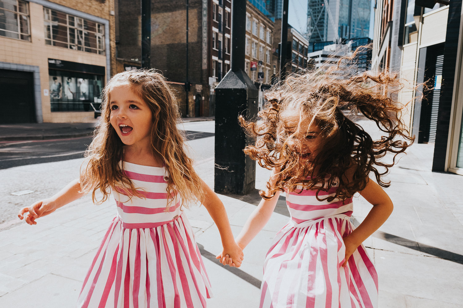 family photo shoot in shoreditch twin girls holding hands in pink dresses