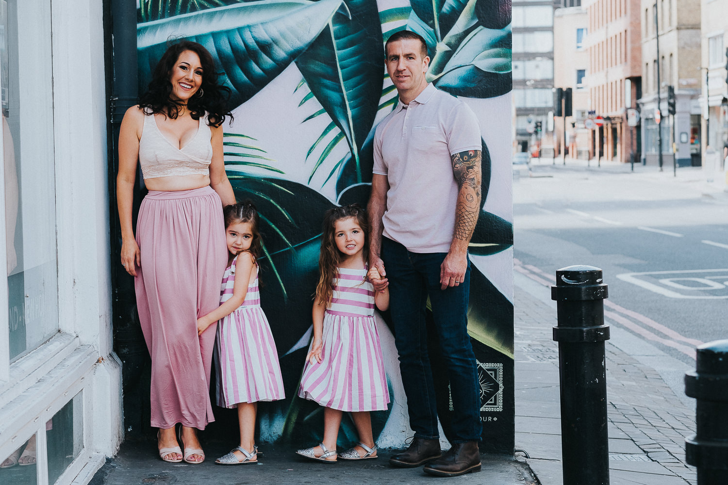 family photo shoot in shoreditch street art twin girls and parents by palm leaf wall