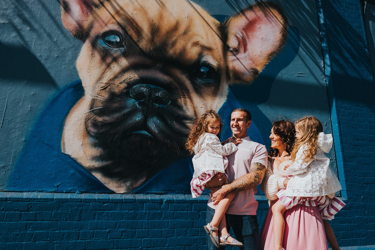 family photo shoot in shoreditch street art dog wall mural twin girls and parents