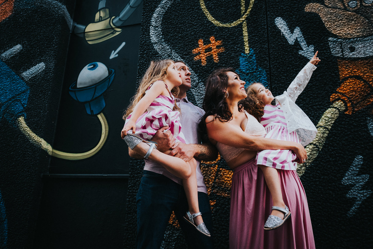 family photo shoot in shoreditch street art robot wall mural twin girls and parents