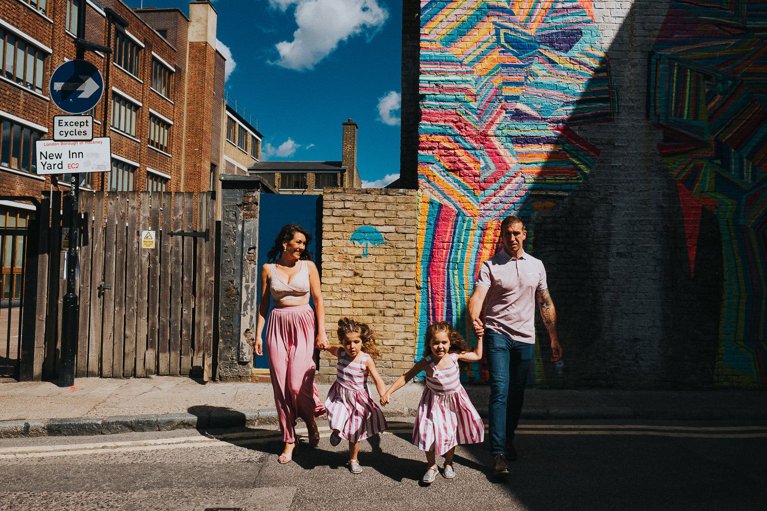 family photo shoot in shoreditch street art twin girls and parents running fun photos