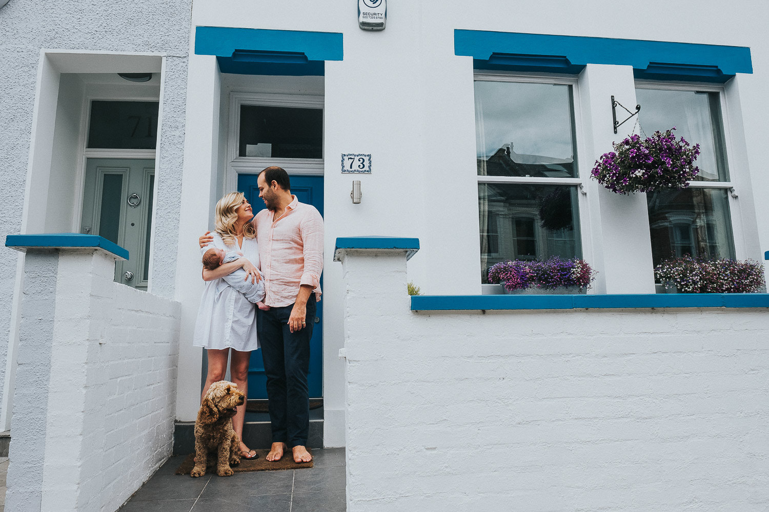 NEW PARENTS BABY AND DOG STANDING OUTSIDE THEIR HOME FULHAM NEWBORN PHOTOGRAPHER