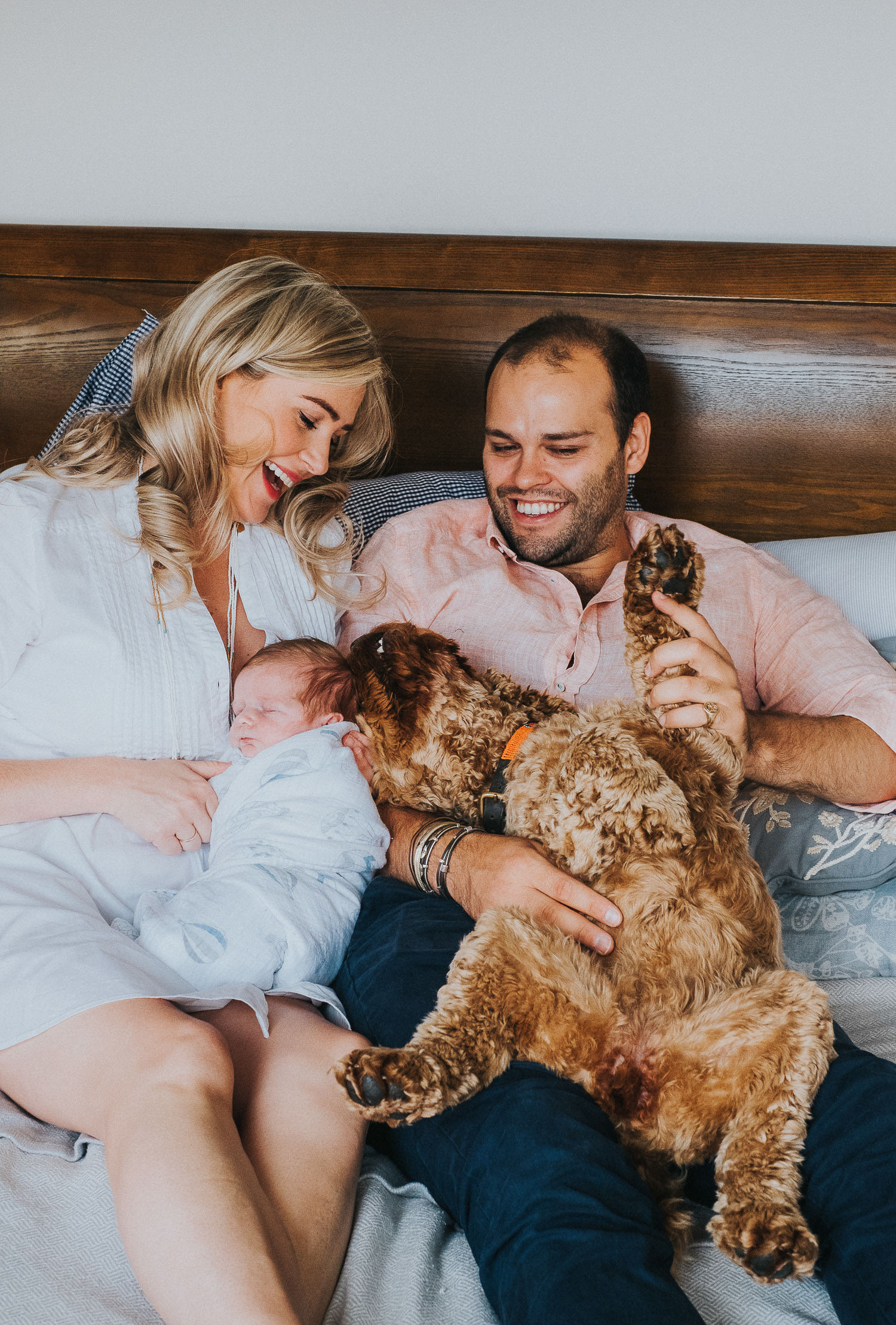 COCKAPOO AND NEWBORN BABY PHOTO SHOOT ON BED FULHAM NEWBORN PHOTOGRAPHER