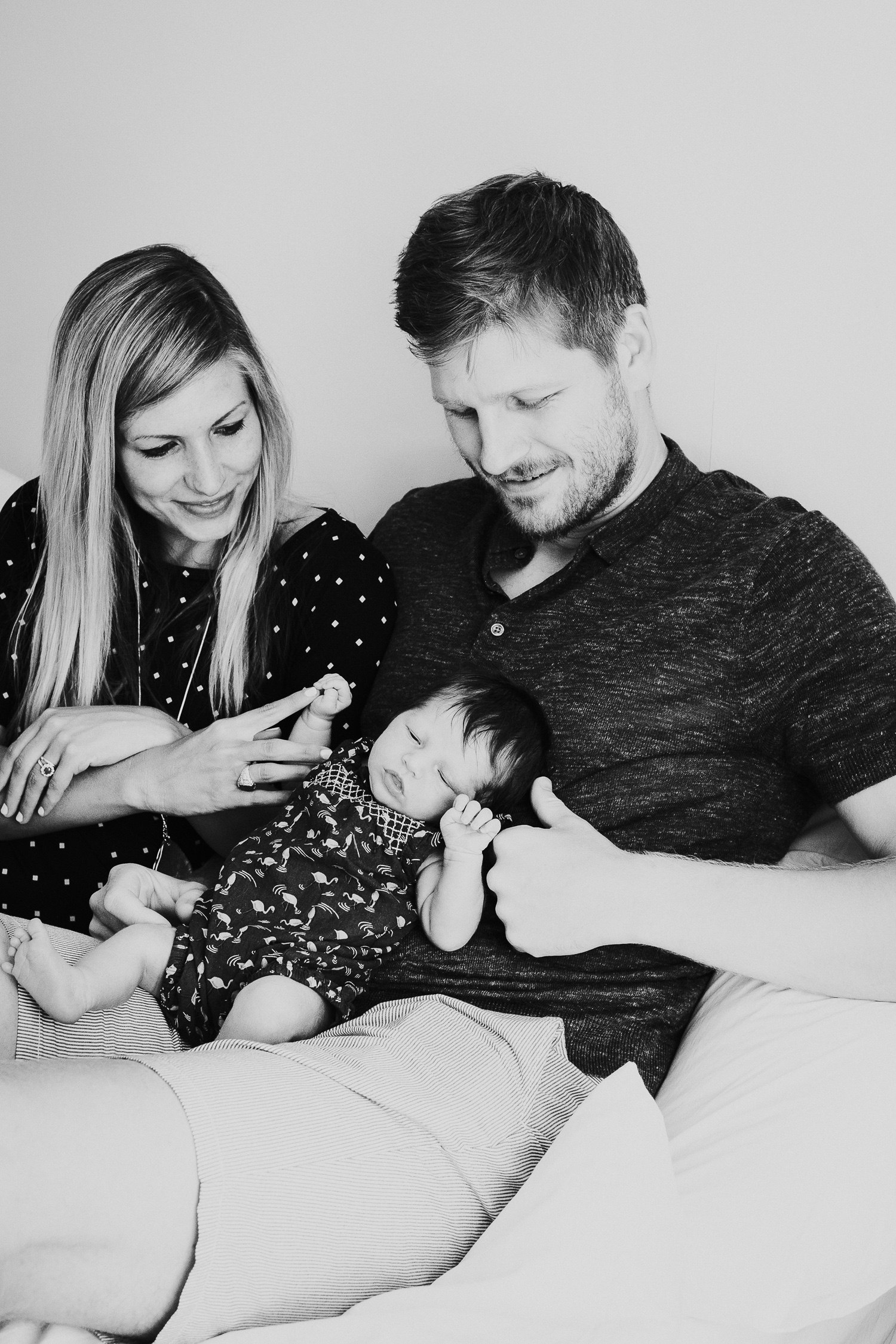 kingston baby photographer black and white photo of new parents with newborn baby on bed