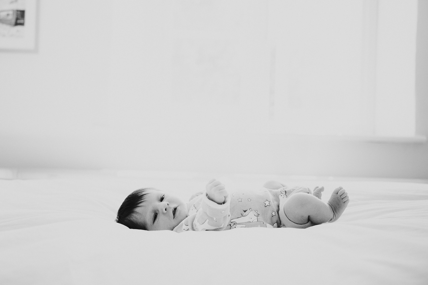 kingston baby photographer black and white photo of baby on bed