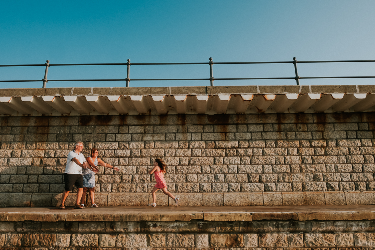 summer family photos in kent child running to grandparents folkestone harbour arm