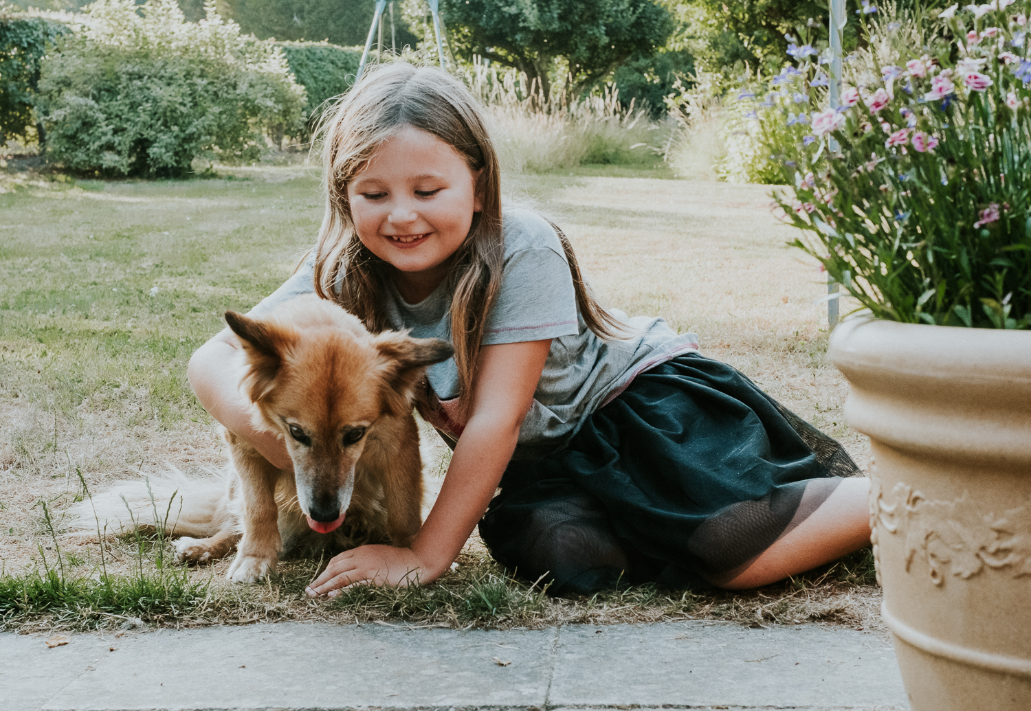 seven year old girl with dog in garden summer family photos in kent