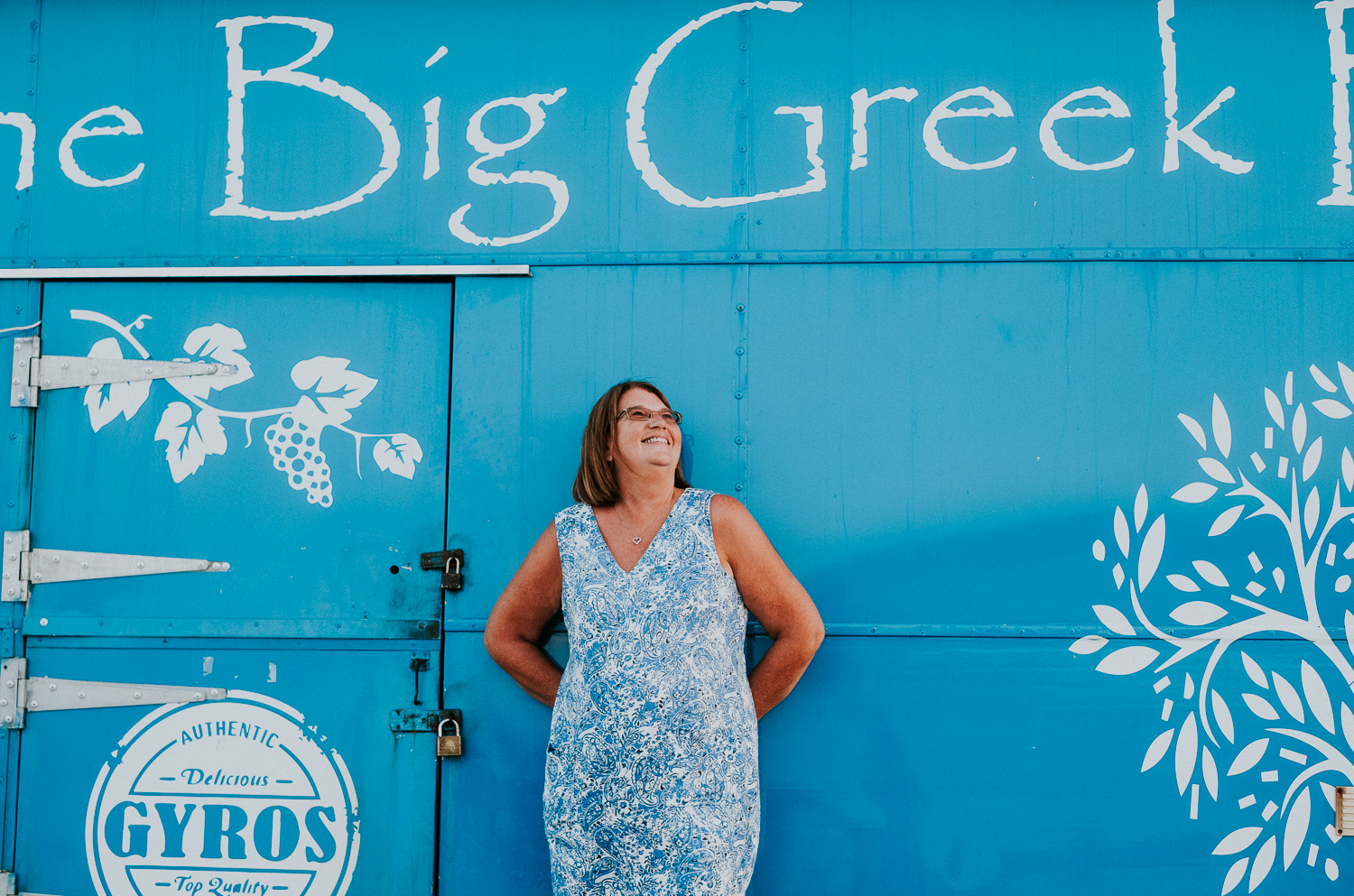 middle aged woman in blue and white dress posing with blue big greek bus folkestone harbour arm