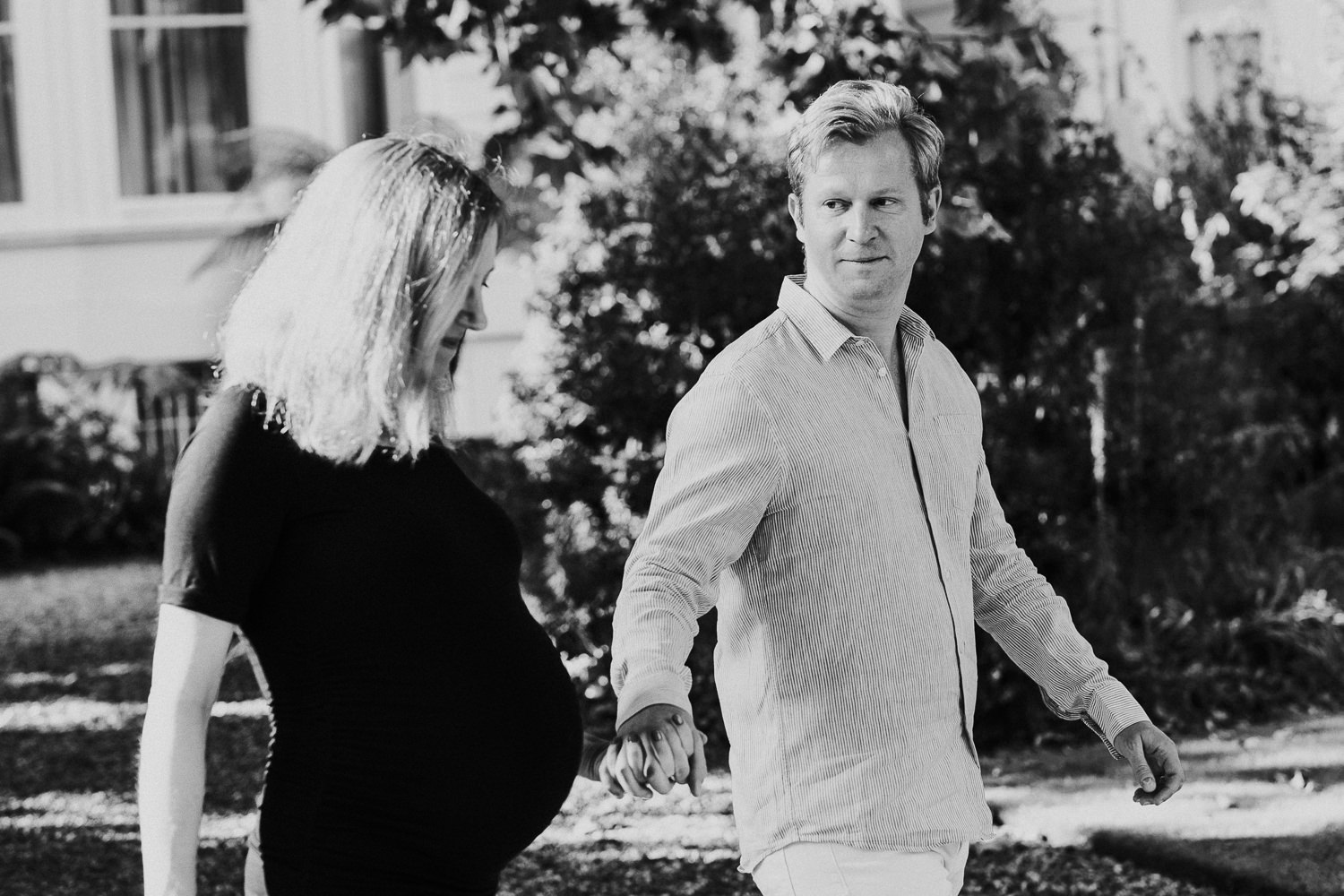 LONDON MATERNITY PHOTO SHOOT pregnant woman and husband walking in garden black and white