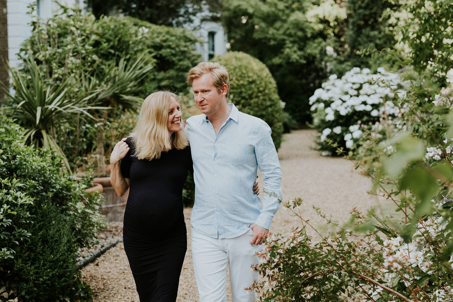LONDON MATERNITY PHOTO SHOOT pregnant woman and husband walking in garden with flowers
