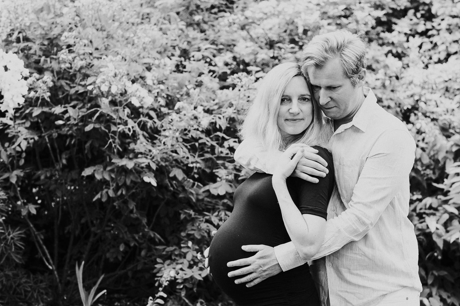 LONDON MATERNITY PHOTO SHOOT pregnant woman and husband hugging in garden black and white