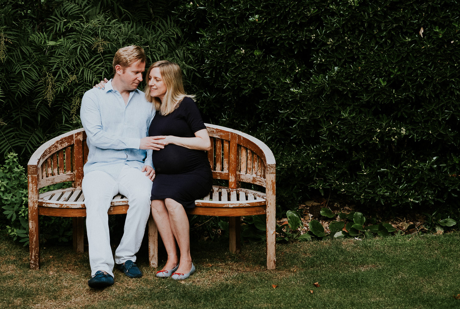 LONDON MATERNITY PHOTO SHOOT pregnant woman and husband sitting on bench