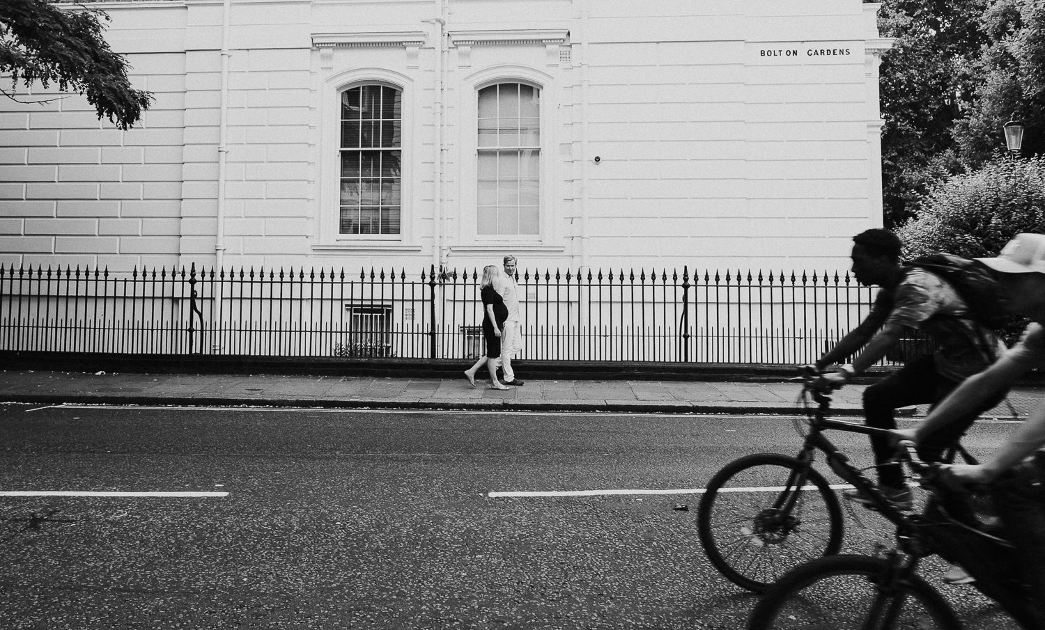 LONDON MATERNITY PHOTO SHOOT pregnant woman and husband walking on street in south kensington london with bicycles