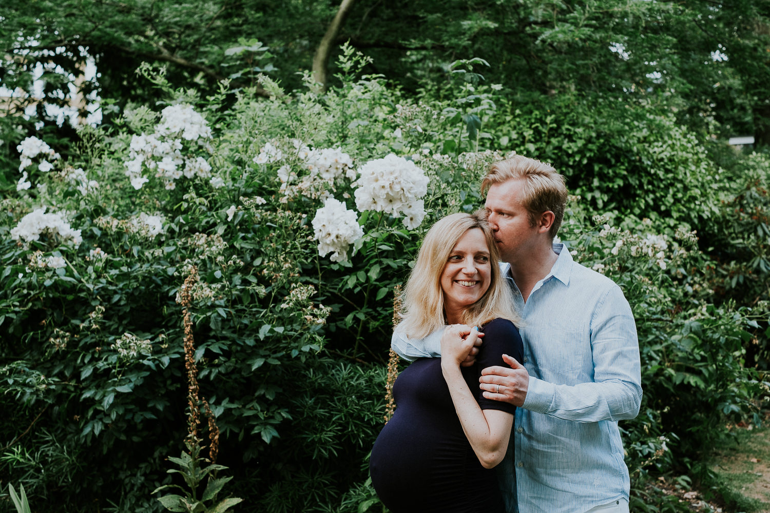 LONDON MATERNITY PHOTO SHOOT pregnant woman and husband relaxing in garden