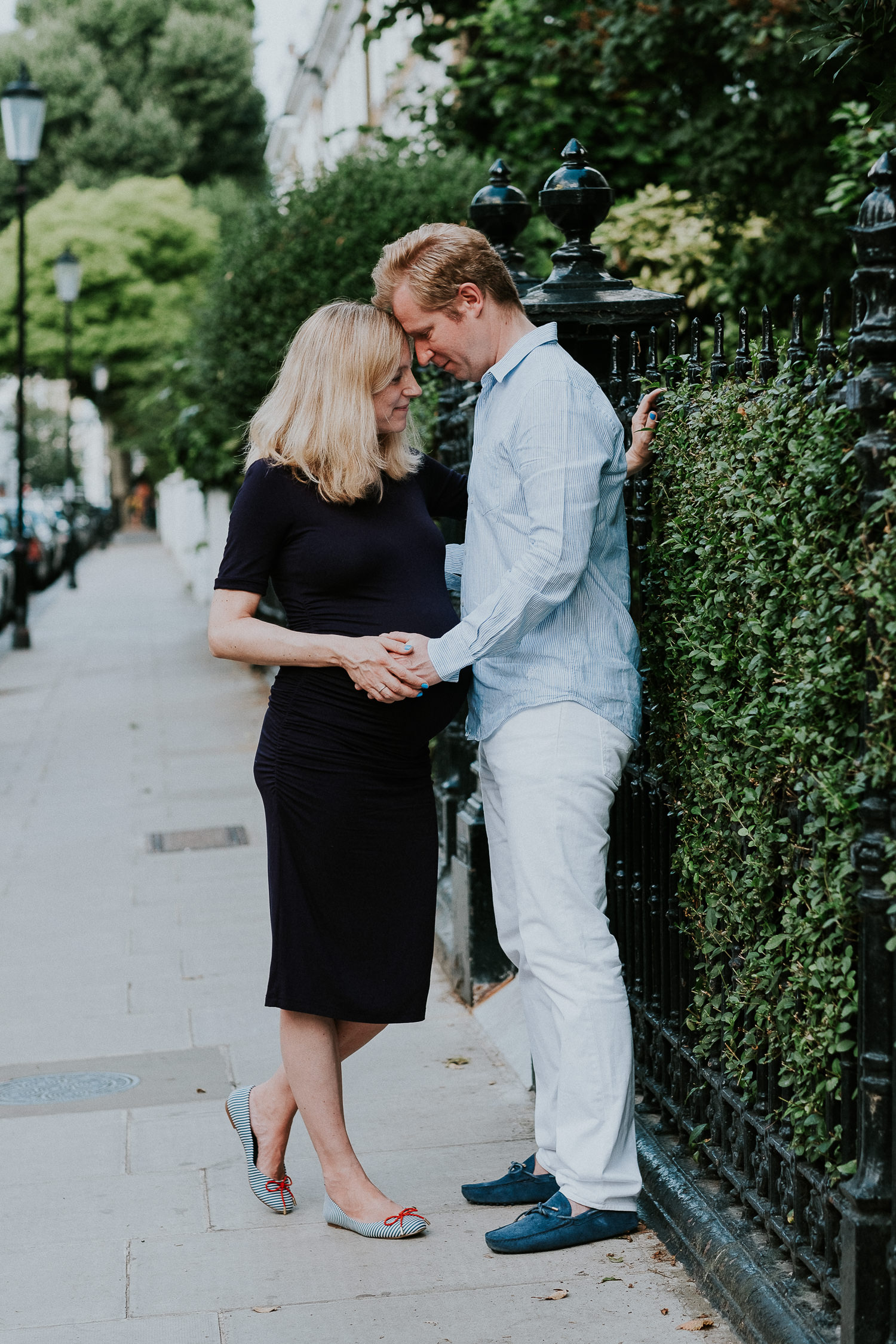 LONDON MATERNITY PHOTO SHOOT pregnant woman and husband embracing on south kensington street