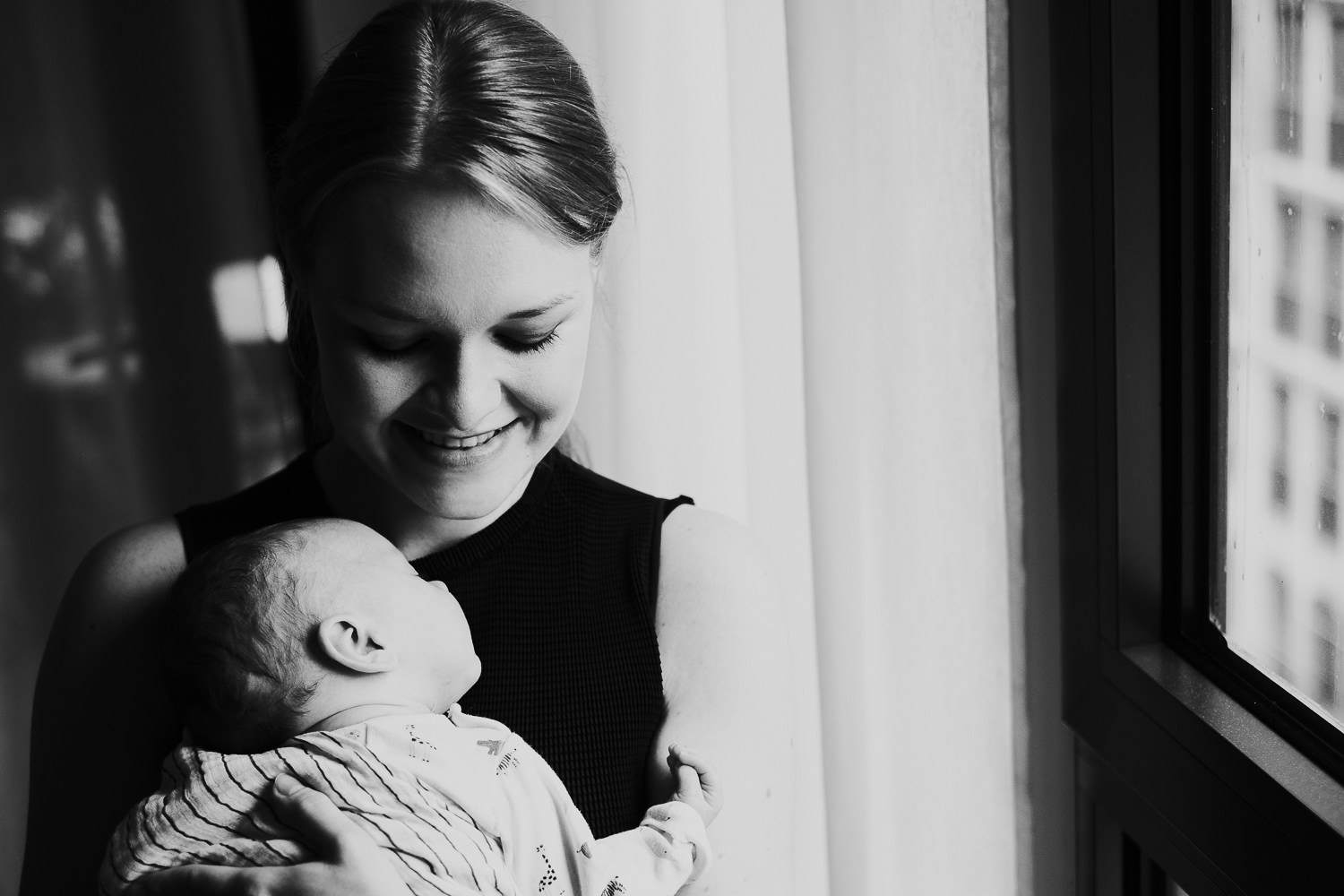 NATURAL LIGHT WINDOW PORTRAIT OF BABY WITH MOTHER BLACK AND WHITE LONDON NEWBORN PHOTOS