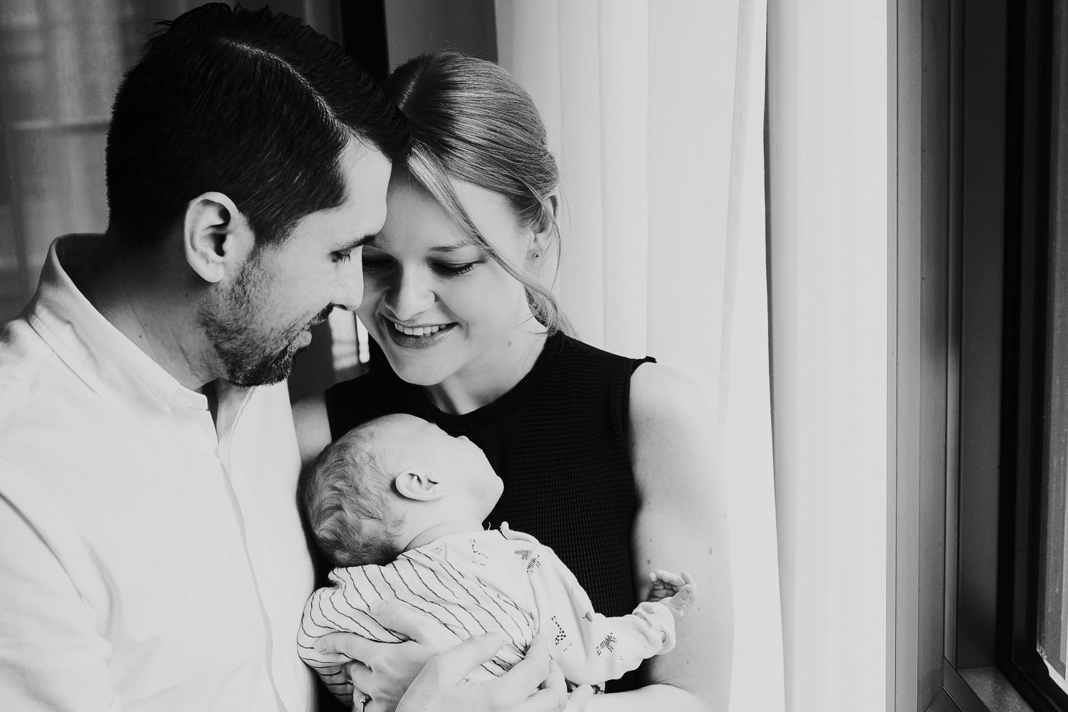 NATURAL LIGHT WINDOW PORTRAIT OF BABY WITH PARENTS BLACK AND WHITE LONDON NEWBORN PHOTOS