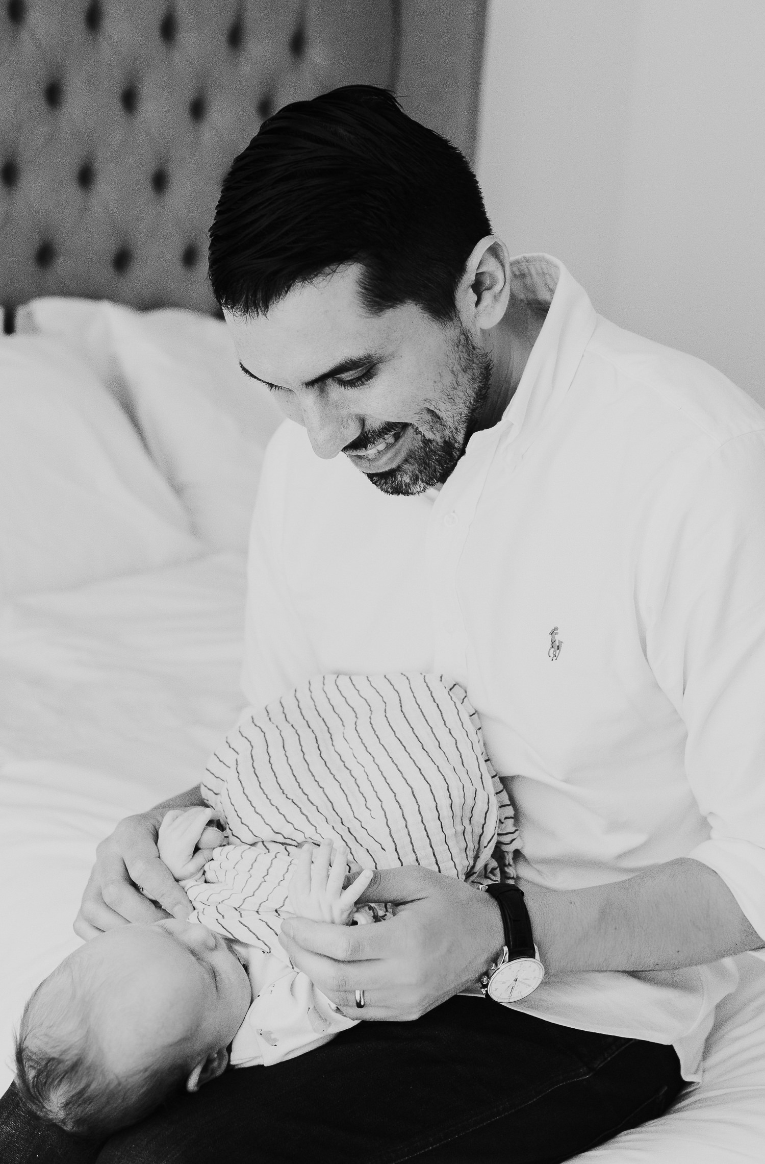 BLACK AND WHITE PHOTO BABY WITH FATHER ON BED LONDON NEWBORN PHOTOS