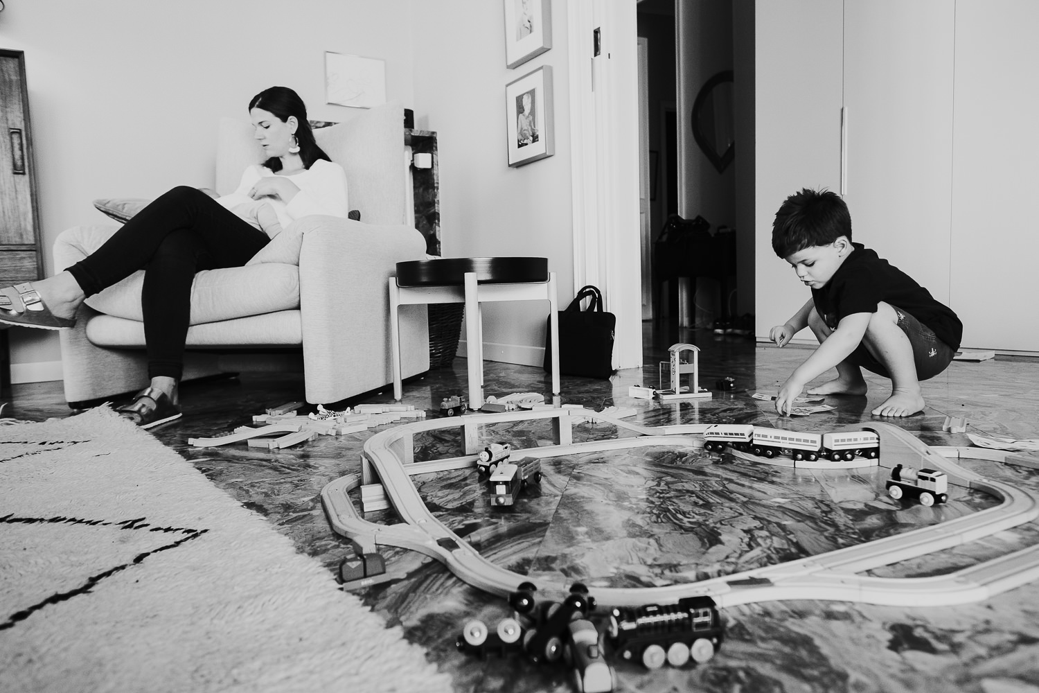 milan family photographer boy playing with toy trains and mother feeding baby