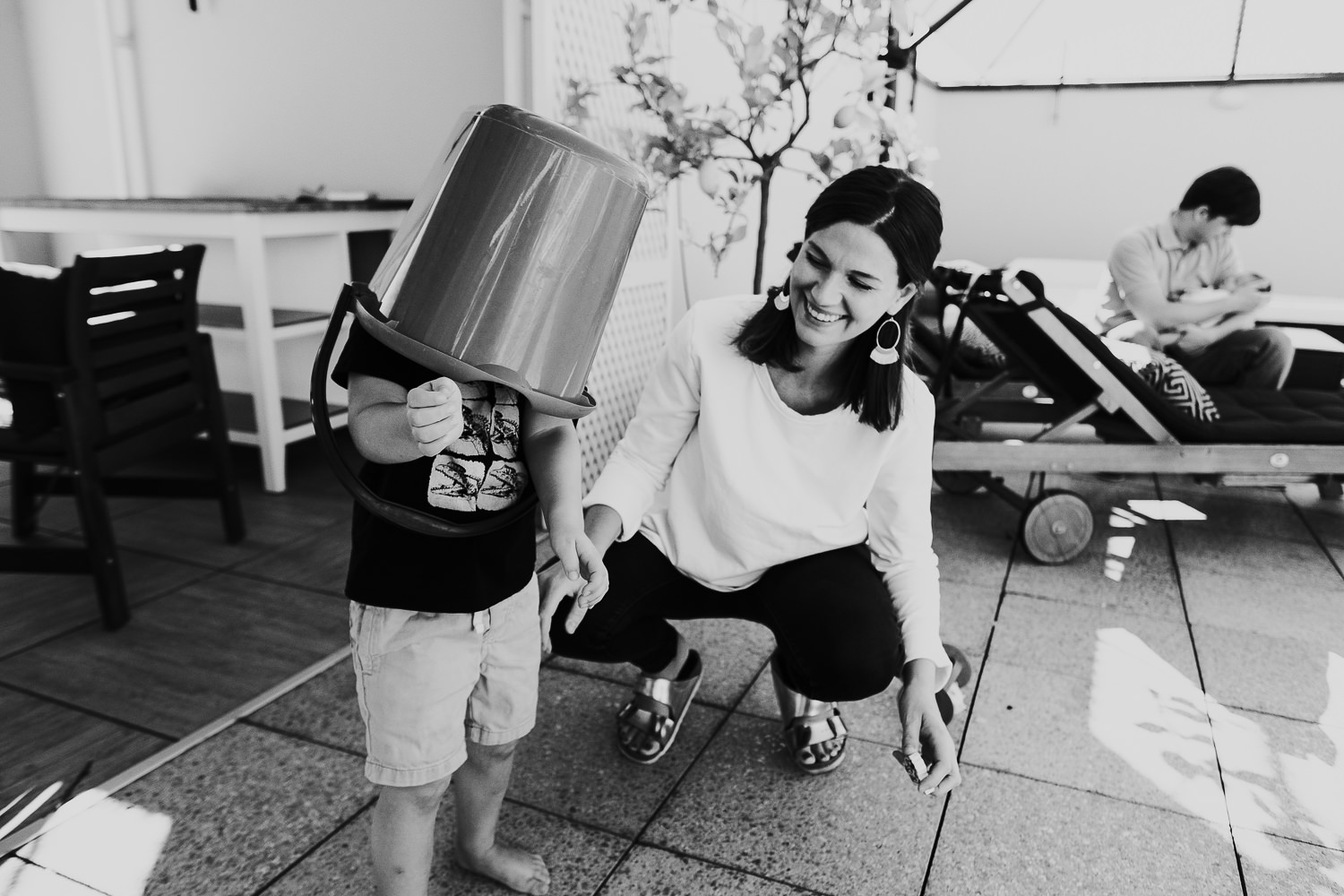 milan family photographer boy and mother playing on terrace with bucket
