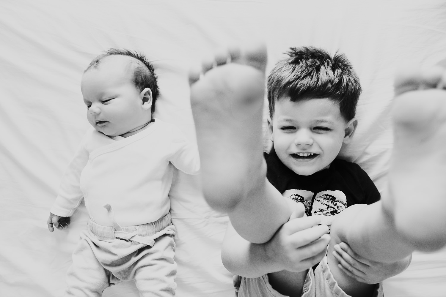 milan family photographer boy and baby brother playing on bed