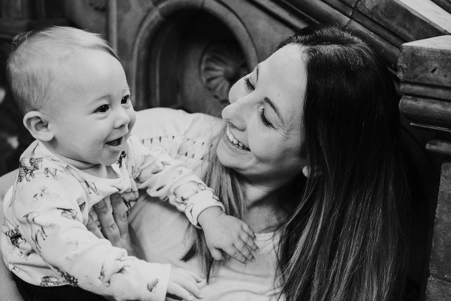 mum and baby son smiling at each other in black and white