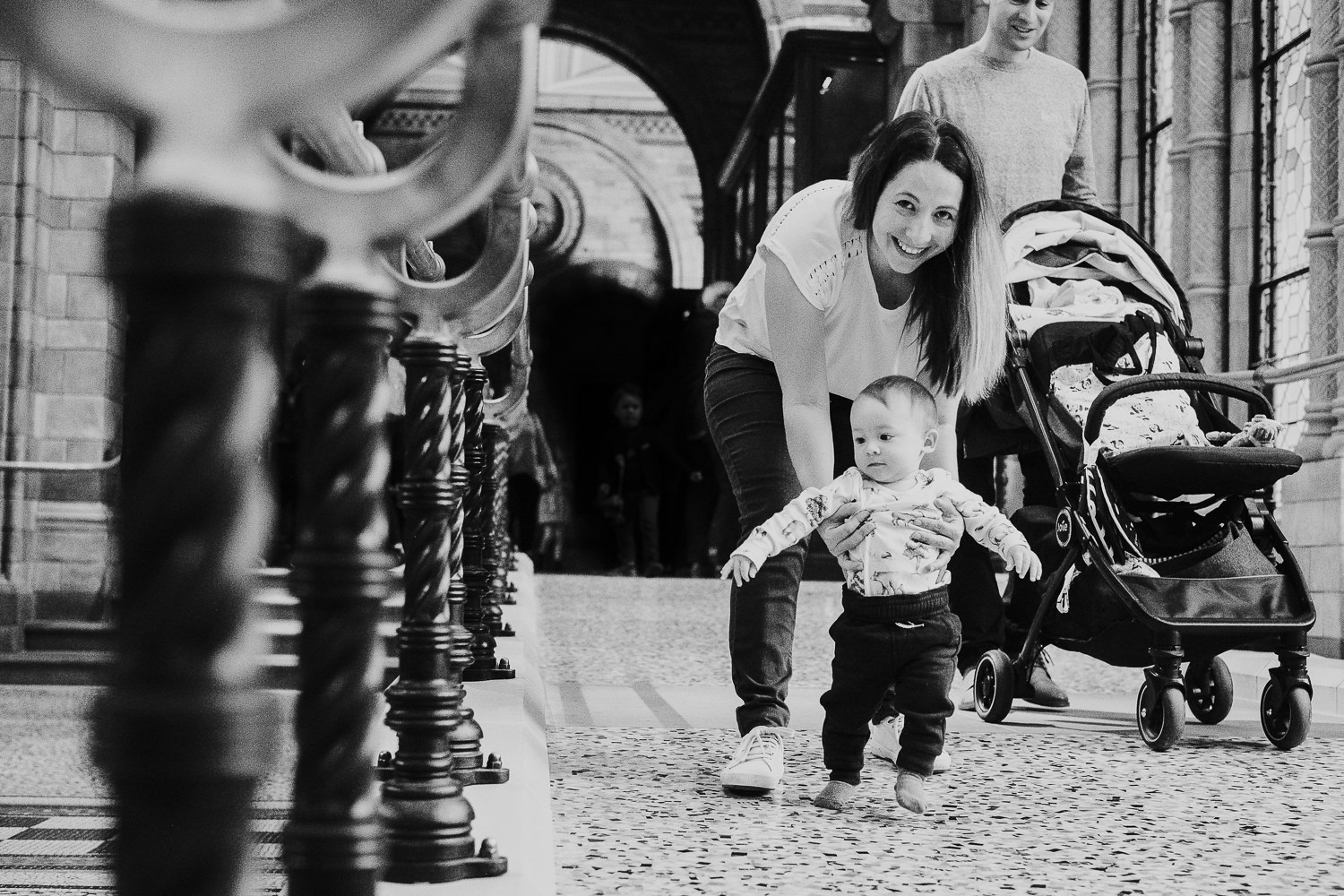 couple walking with toddling baby son at the natural history museum family photography