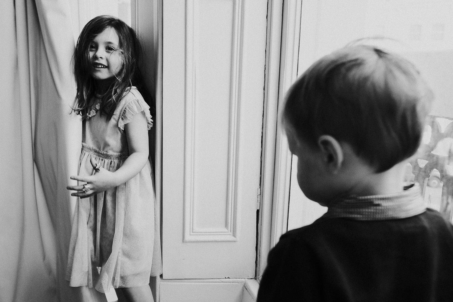 notting hill family photographer portrait of girl and brother hiding behind curtain