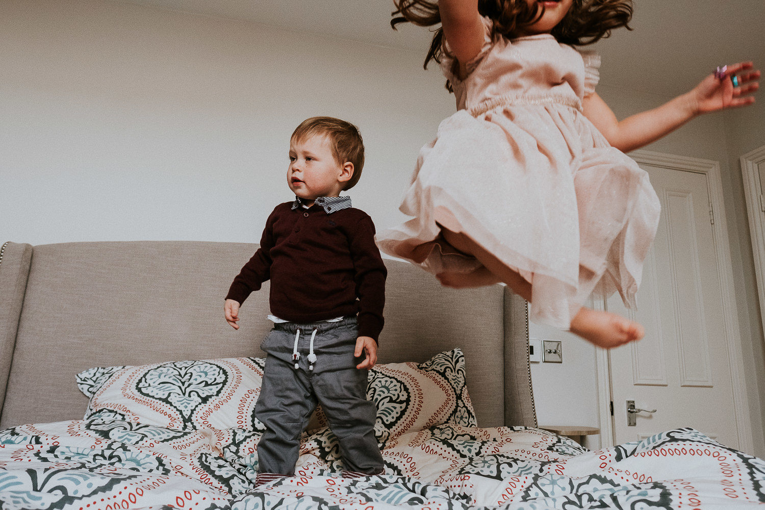 notting hill family photographer portrait of girl and brother bouncing on bed