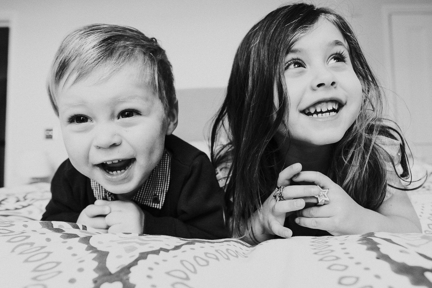 notting hill family photographer portrait of girl and brother lying on bed laughing