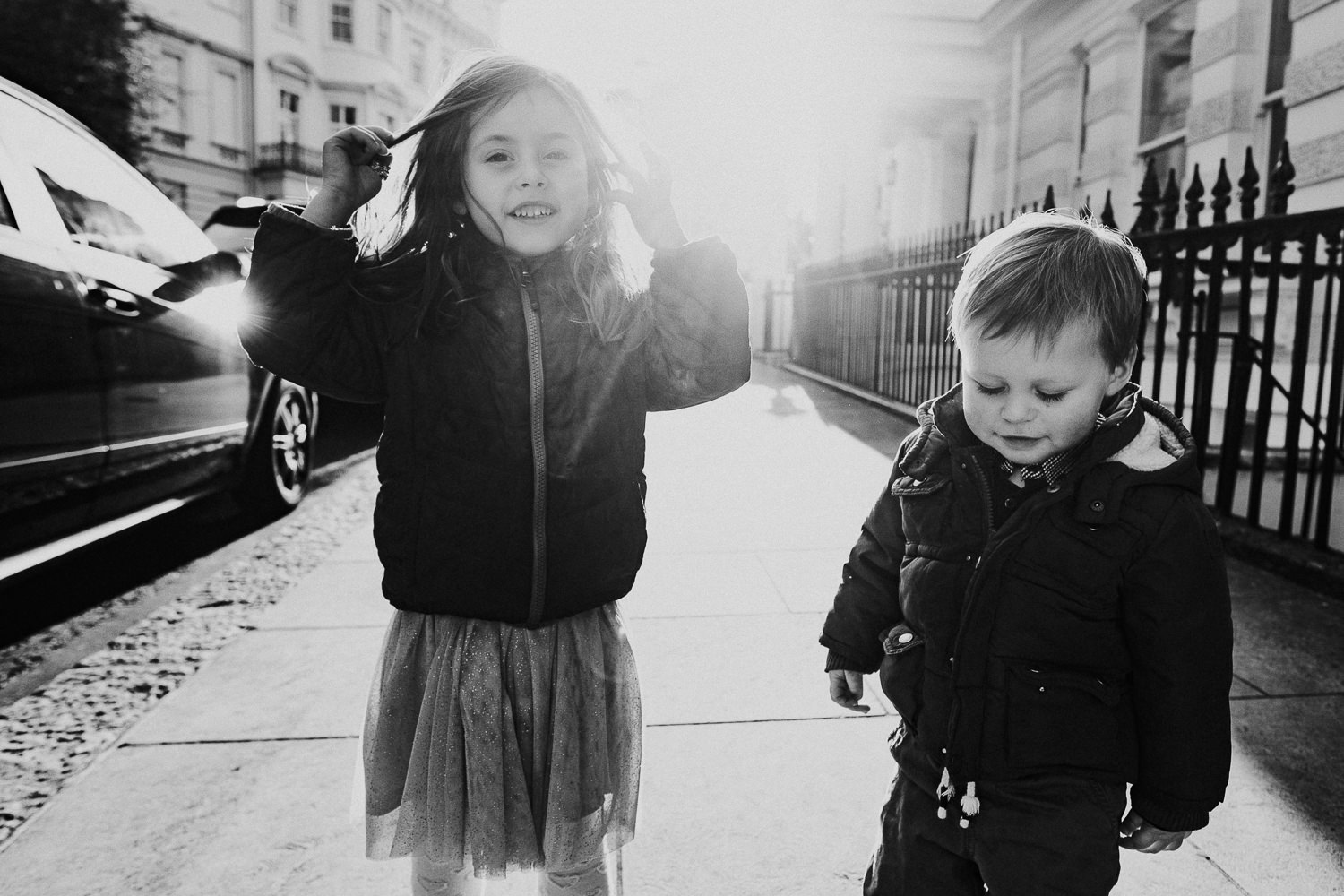 notting hill family photographer portrait of girl and brother outdoors sun flare