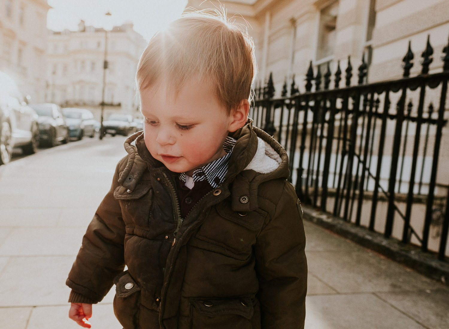 notting hill family photographer portrait of boy outdoors on London with sun flare