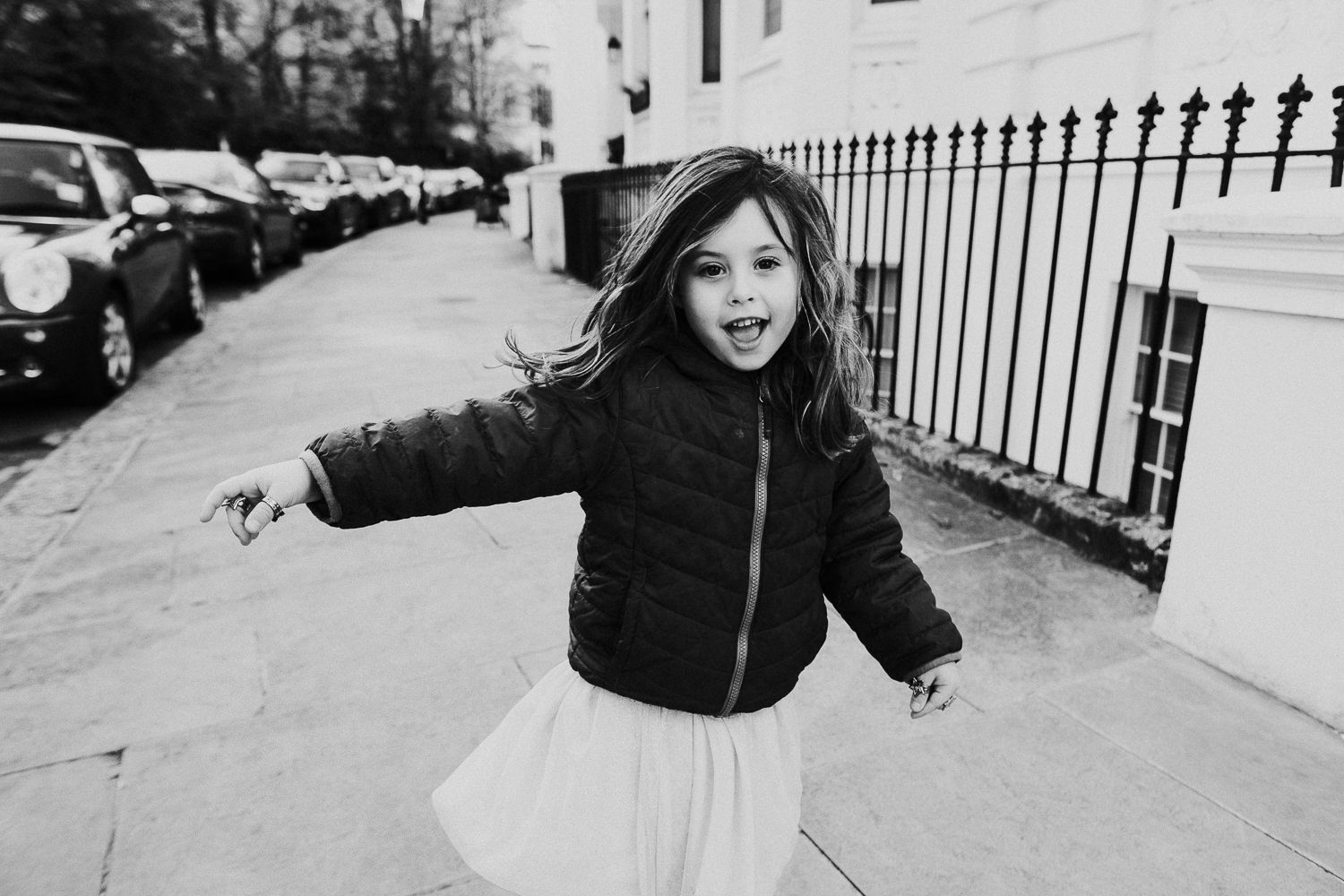 notting hill family photographer black and white photo of young girl dancing in the street