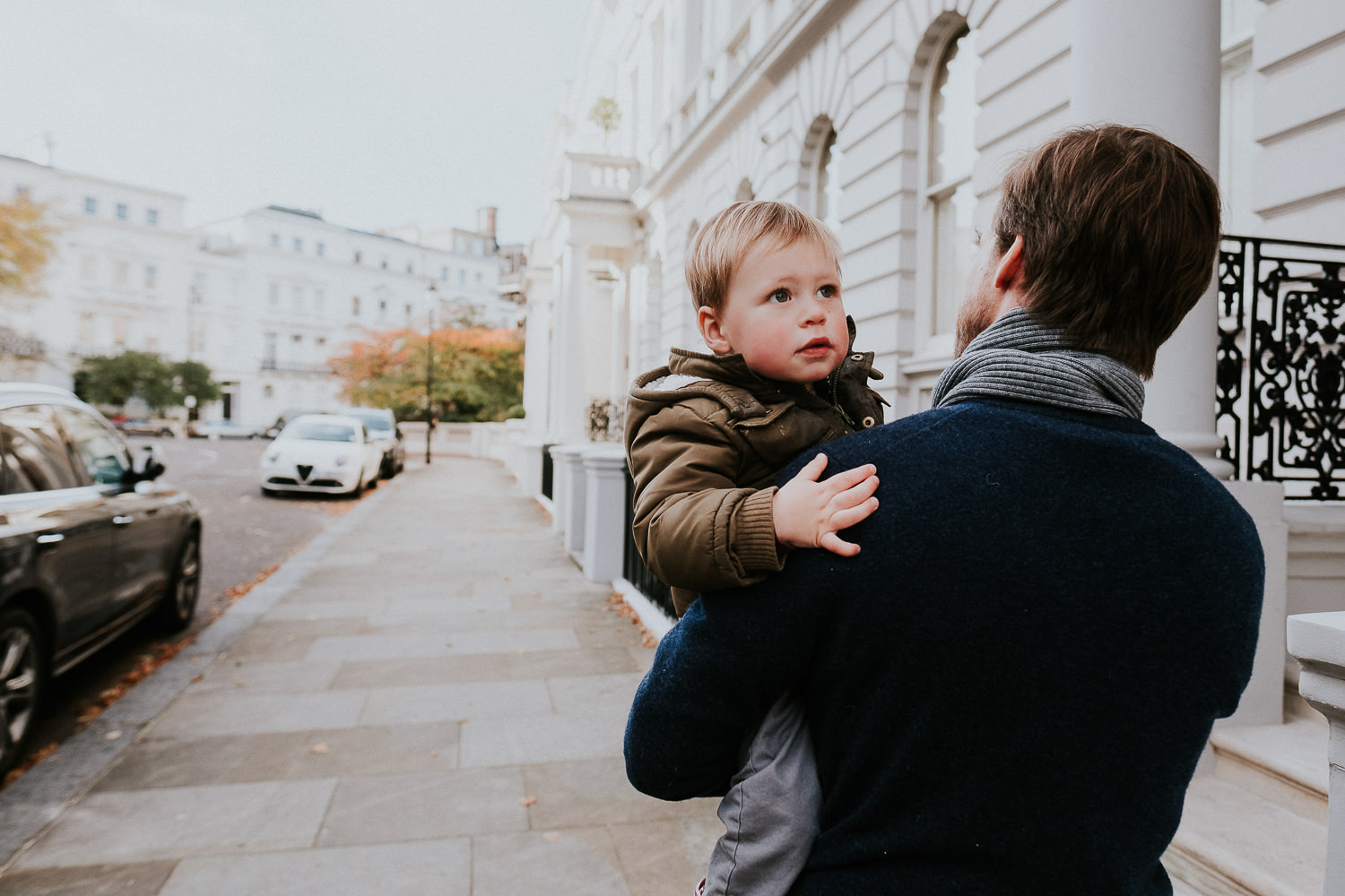 notting hill family photographer father carrying son in arms on London street