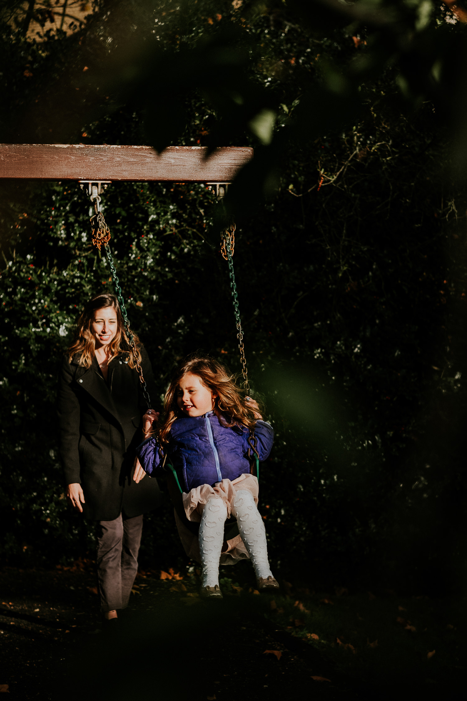 notting hill family photographer young girl being pushed by mother on swing
