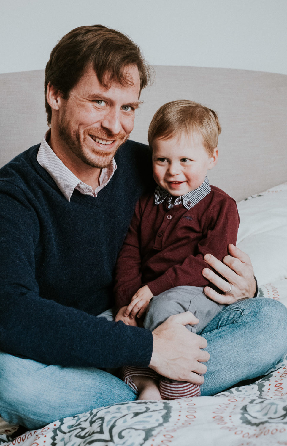 notting hill family photographer father and toddler son portrait sitting on bed