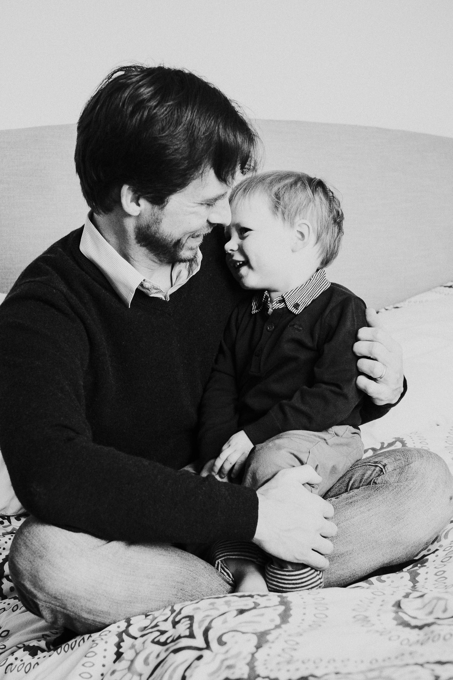 notting hill family photographer black and white portrait of father and son sitting on bed laughing