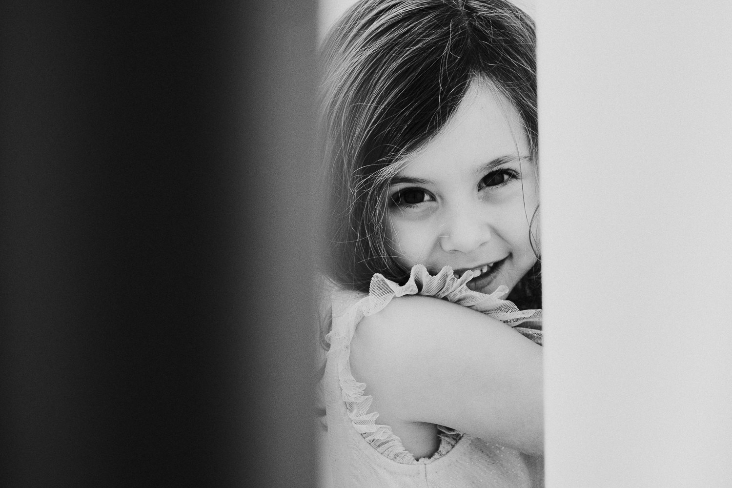 notting hill family photographer portrait of girl hiding behind curtain