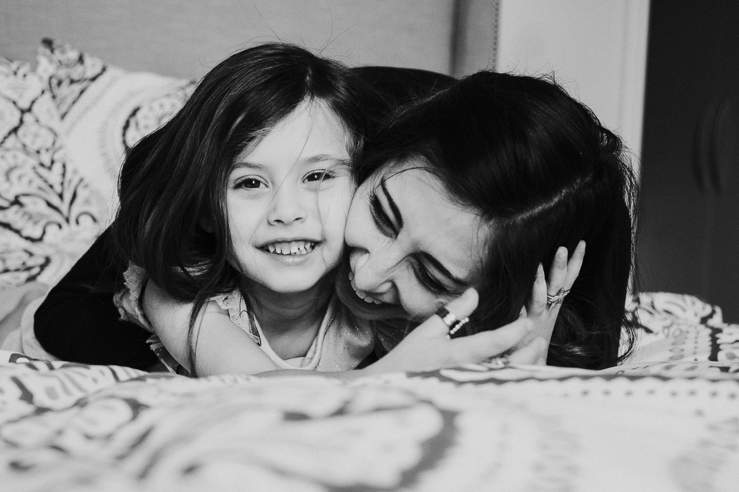 notting hill family photographer young girl with mother lying on bed