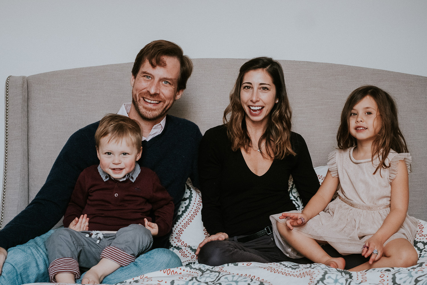 notting hill family photographer family portrait sitting on bed toddler boy and young girl with parents