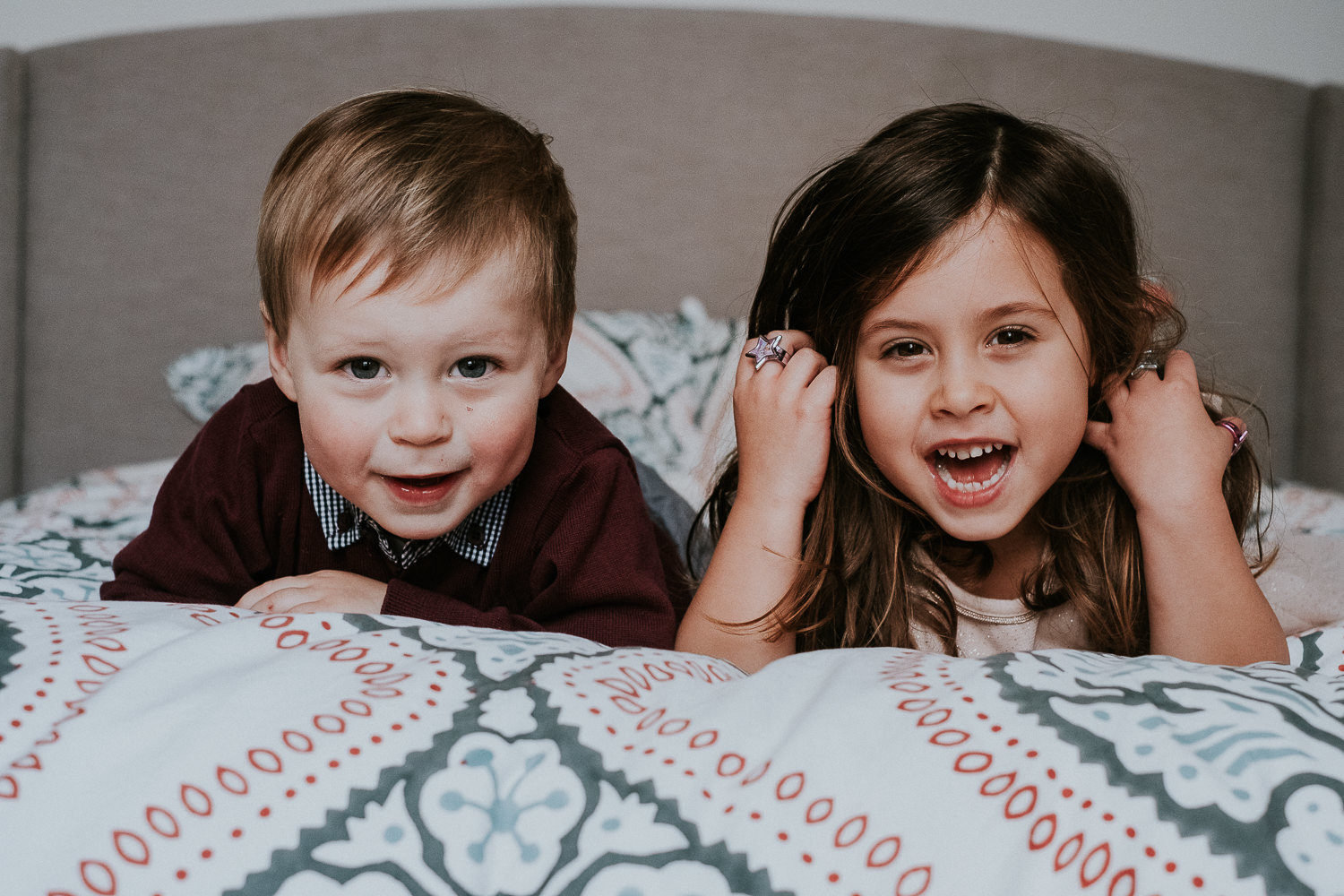 young girl and toddler brother portrait on bed laughing