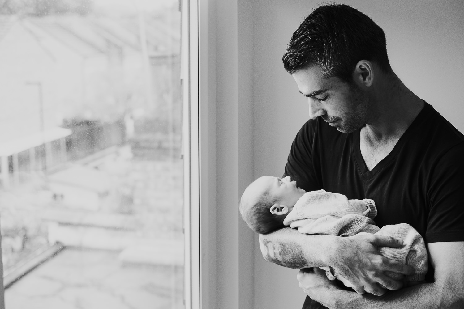 father holding baby son black and white photo london newborn photography
