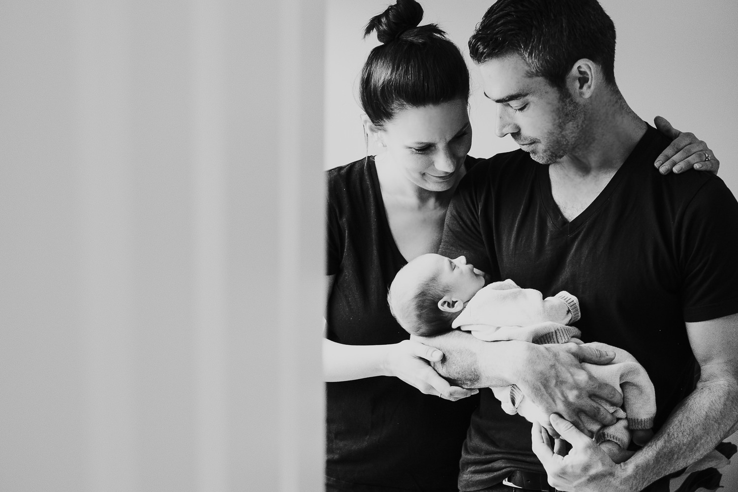 new parents holding baby son black and white photo london newborn photography