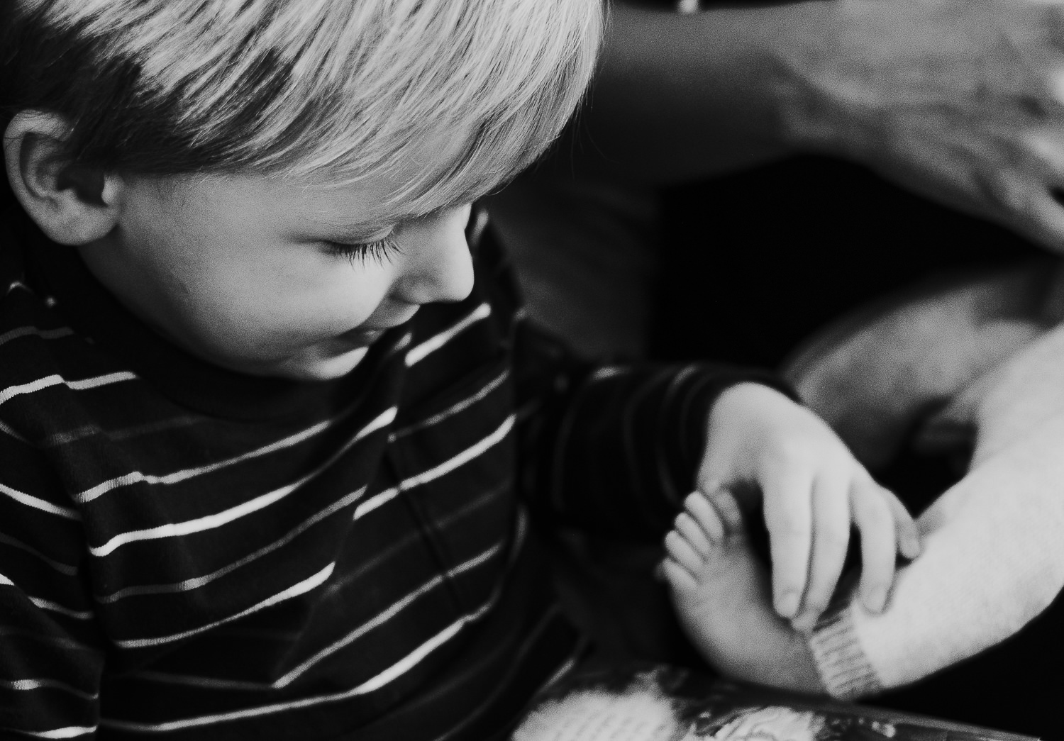 toddler boy holding baby brothers foot black and white photo london newborn photography