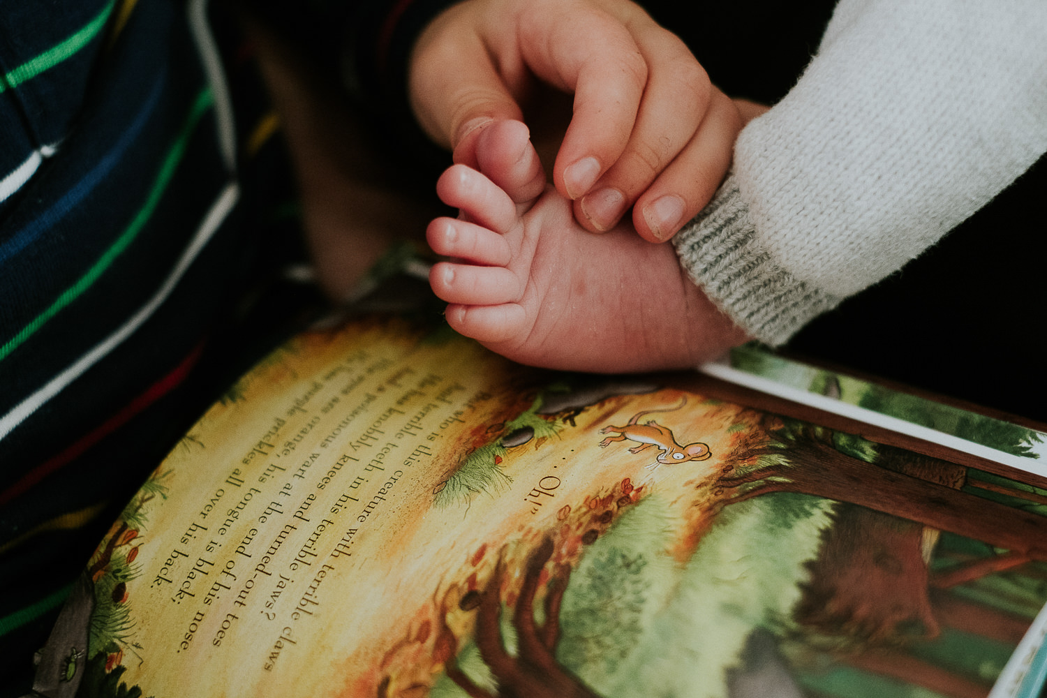 toddler brother holding baby's foot london newborn photography